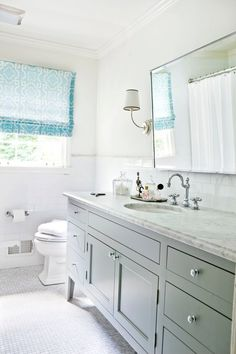 Melanie Turner Interiors Sunny bathroom design with gray extra wide bathroom vanity with marble countertop, rectangular pivot mirror, Vendome Single Sconce, marble mosaic tiles floor, polished nickel faucet kit, subway tiles, backsplash and blue geometric pattern roman shade.