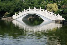 This incredible and ornate white bridge stands out against the backdrop of thick ornamental trees and is reflected in the still surface of a large pond.