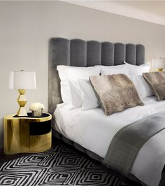 A gorgeous black, white and gray master bedroom design with a golden Wave Nightstand bringing its charm over a chevron rug.