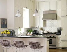 Love this white kitchen! White steel mesh bar stool subway tile & industrial light fixture