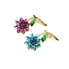 """DESCRIPTIONBlue and Purple Scatter Pin Brooch SetBright Pom Pom Style Flowers accented with a sparkling radiant cut rhinestone centerComplimentary colors with a soft pearl finish to the painted enamelBeautiful Amethyst Purple , lovely sky blueGold Tone Stem with light green enamel painted leaveDETAILS1960s EraSet of Two BroochesPainted Blue and Purple EnamelGold Tone Pin BackExcellent Vintage Condition MEASUREMENTS2 1/2"""" x 1 1/8"""""""