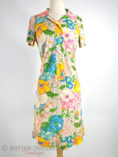 Nearly neon, slightly psychedelic flowers in pink, yellow, blue and green rest on a background of printed purple ruffly ribbons. Shirtwaist shift with five-button half placket, hook&eye under pointed