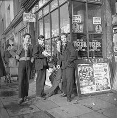 Nigel Henderson, Photograph of four young men outside a shop in East London c. 1951 © Nigel Henderson Estate