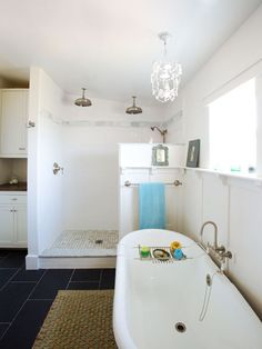 A doorless shower and bright-white plate-rail-capped wainscoting give this bath an airy feel. Porcelain floor tiles offer the look of slate for less.   Photo: Susan Seubert   thisoldhouse.com