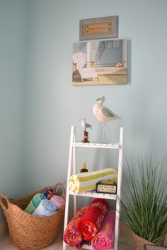 Vignette for a pool bathroom. Store the beach towels in a decorative way.