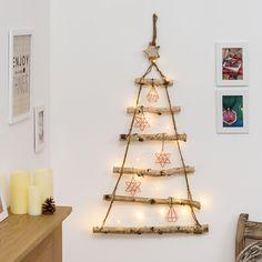 Albero di Natale in legno con catena di luci natalizie e decori in rame in stile scandinavo