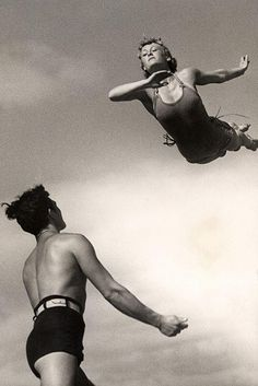 Man standing ready to catch a woman coming down with a swallow dive, 1937.