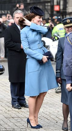 Blue breeze: The wind appeared to be causing havoc with Kate's tresses outside the church this morning