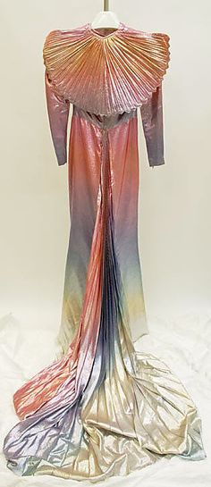 Rainbow lamé fancy dress costume (back, with pleated cape) by Thierry Mugler, French, 1981.