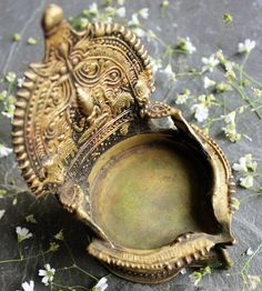 This is a Hand crafted Vintage Kamatchi Vilakku - A divine brass lamp with the figure of Goddess or Devi Kamakshi engraved on the lamp and found in most Indian households. Before lighting, the lamp is traditionally decorated with flowers and other sacred items. One can find the Kamatchi Vilakku kept by families for generations and preserved as a precious ornament. It is said that some families still keep the Kamatchi Lamp burning from the time it was lit by their ancestors. The Deepamor the…