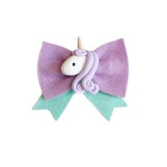 "Adorable lavender wool felt bow measuring at 3"" across and 2.5"" top to bottom including mint tails. Adorned with a hand made polymer clay unicorn ! Please allow 3-4 weeks for production."