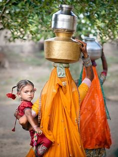 A child on her hip, pots of water on her head - a woman's load