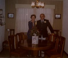 A picture of my mother and father on their 25th wedding anniversary.  Their wedding picture is on the table in front of them.