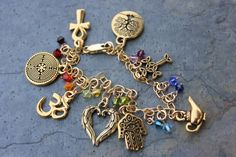 ancient religions charm bracelet - om (aum), Celtic cross, tree of life, hamsa hand, angel wings, genie lamp, ancient labyrinth, & ankh charms - representing the truths and mysteries of ancient and modern religions.