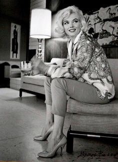 A smiling Marilyn Monroe is photographed in her home.
