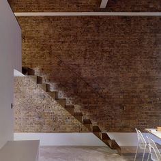 A sheet of steel measuring just six-millimetre-thick was folded and welded before being finished with a coating of atomised brass to create this staircase by London-based Bell Phillips. A matching handrail runs along the existing brick wall, while the other side is left unguarded.
