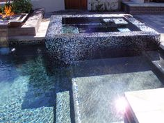 This backyard renovation is complete with a beautiful all-tile, perimeter-overflow spa. The spa is finished in a black iridescent glass tile. It looks black from one direction, but it seems like 100 different colors when the sunlight shines on it.