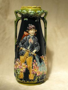 A large, well potted Majolica vase with an uncharacteristic human theme.  Against a dark emerald green background a young, pink cheeked gardener waters flowers from a backpack water tank. Organic Art Nouveau designed top and handles, multicolor glaze effects