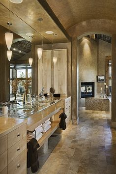 Travertine bathroom with great towel storage under the glass sinks.
