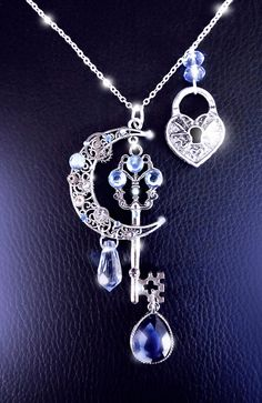 Moonlight secrets Mysterious, sparkling and so magical, this baby blue/blue grey and silver moonlight goddess key necklace is a unique, dreamy neck adornement. Featuring silver watch gears, filigree detailing, crystals, rhinestones, and lots of sparkling silver, you will feel like a magical moon goddess wearing this unique piece. Truly one of a kind, this highly detailed, very shiny necklace is so stunning to look at and is guaranteed to get compliments. Perfect for anyone who likes int...