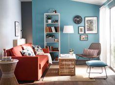 明るいリビングルームにオレンジの3人掛けソファベッド、籐製のアームチェア、ターコイズのフットスツールとアカシア無垢材の収納付きテーブル