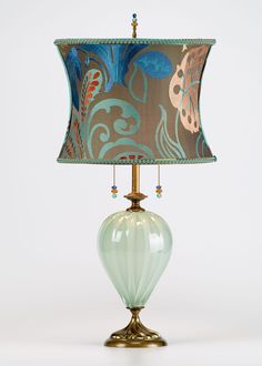 Kristen by Susan Kinzig and Caryn Kinzig (Mixed-Media Table Lamp) Mixed-Media Table Lamp - Table lamp, large sea foam colored blown glass, round shade covered in colorful contemporary floral fabric, double bulb socket, beaded pulls and finial. Chandelier Lamp, Chandeliers, Rustic Lamp Shades, Media Table, Lampe Decoration, Tiffany Lamps, Bedroom Lamps, Lampshades, Lamp Light