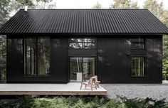 Clad in corrugated steel, this shiny black house features a spacious deck that's ideally suited for ... - Appareil Architecture