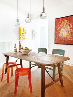Modern + Functional // Madrid apartment with bright light eating space + mix and max chairs and stools + rustic vintage wood table + art