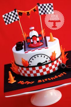 Go Kart Cake - A cake for a birthday boy having a go-karting party. Everything modeled from fondant except the edible image flags. Dental floss holds up the bunting.
