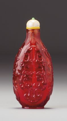A RUBY-RED GLASS 'KUI DRAGON' SNUFF BOTTLE ATTRIBUTED TO THE IMPERIAL GLASSWORKS, QING DYNASTY, QIANLONG PERIOD