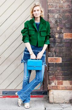 Zanita wears a bright green cropped jacket, denim top, blue jeans, sandals, and a blue top handle bag