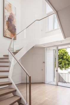 A glass railing flanks the curved, floating staircase. Glass Stairs, Glass Railing, Stair Photo Walls, Tropical Interior, Modern Tropical, Floating Staircase, Glass Balustrade, Build Your Own House, Curved Glass