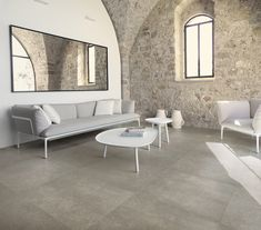 Rustic living room design with stone walls and porcelain tile flooring