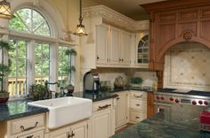 Kitchen Remodel, Daniels Design and Remodeling, dark cabinets, light cabinets, bright lighting,glass cabinets, island,  dark countertops, open space, luxurious, hardwood floors, contemporary, granite countertops, hanging lights, light colored walls, deep white sink, spiral staircase, elegant trim,arch hallway,