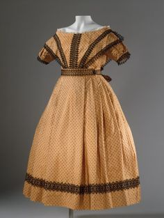 Girl's Dress with Pelerine England, circa 1869 Costumes; ensembles Silk .1) Dress center back length: 36 in. (91.44 cm); .2) Pelerine center back length: 14 in. (35.56 cm); .3) Sash length: 25 in. (63.5 cm); .4-.5) Sleeve length: 15 in. (38.1 cm) each http://collections.lacma.org/node/184281