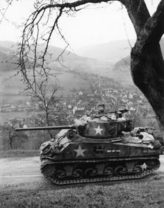 "In a kinetic image, a U.S. Army 12th Armored Division M4A3(76)W Sherman medium tank nicknamed ""WAS IST DAS"" (""What is that"" in German) races through Schneeberg, Germany (1945)."
