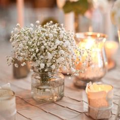 small jars of babies breath, votive candles and mercury glass candles scattered around table.