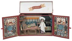 "French kitchen play set, ca. 1900.   6"" x 10"" closed. A heavy cardboard box with red paper cover, hinges open at the top to reveal gilt-lettered sign ""Cuisine"", and at the front to reveal a well-equipped kitchen, having ""tiled"" walls, tinplate stove with matching ""tile"" front design, shelves supporting a wide assortment of enamel cookware, supplies, and food suppliers, wooden table and chairs with red-checkered paper covers, and a bisqueheaded doll with chef's apron, shirt and cap."