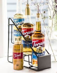 We're sort of obsessed with this fantastic way to display & share your Torani syrups. Put a pump or pour spout in them & then everybody can enjoy flavored coffees from your at home coffee bar! :)