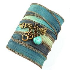 This Om silk wrap bracelet features an antique brass Om, Buddha, hamsa, and genuine wire wrapped turquoise teardrop bead on a hand painted silk ribbon in beautiful shades of blue.