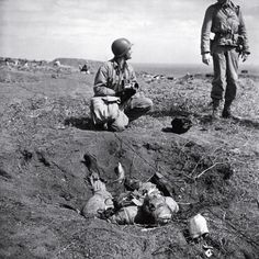 <b>Unpublished.</b> American troops chat near a dead Japanese soldier on Iwo Jima. The degree to which the Japanese were willing to fight to the death, rather than surrender, is summed up in one remarkable statistic: Close to 20,000 Japanese soldiers were killed during the battle