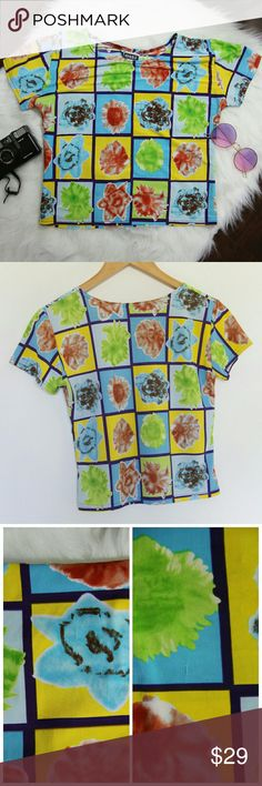 "90's vintage colorful pop art flowers top size L Amazing colorful shirt with flowers printed on inspired by pop art. Top is made out of stretchy material and is super comfy.  Size: Large Materal: Nylon, Spandex Brand: Jessi Condition: Good vintage condition, shirt has some distress all over on front and back (shown in close up photos)  but are very small and barely noticeable. Gives a rad grunge look.  ~MEASUREMENTS~  (taken laying flat)  Length: 19"" Chest: (underarm to underarm) stretches…"