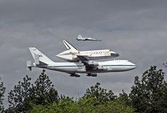 DC SHUTTLE by David F. Brown    Space Shuttle Discovery makes a low pass in front of the National Air and Space Museum, Dulles International Airport prior to landing there. Note the T-38 Talon chase/camera ship along side.