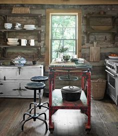 In this Tennessee cabin, an industrial worktable, topped with custom-cut glass, serves as the kitchen's island; the stools were also rescued from a factory. A vintage zinc icebox offers hidden storage, while open Douglas-fir shelves hold dishes and cookware. The stainless steel stove is Jenn-Air.   - Delish.com