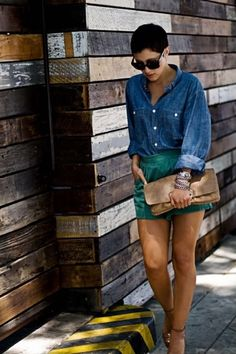 Denim button top with sleeves rolled up, green mid-waist shorts and brown heeled sandals with a nautral nude clutch and silver bangles