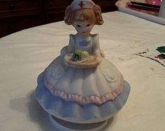 """1970s nurse music box made by Precious Price Products. Pretty light brown haired nurse is wearing an old fashioned dress of blue, white and pink, and is wearing the traditional hat with red cross. She is carrying a tray of objects and is on a rotating stand. The music box works well and plays """"You light up my life"""". Great gift for nurses graduation. She is 4"""" X 4"""". In great vintage condition with no chips."""