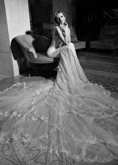 #GaliaLahav -- Madison is a mermaid style gown with glamorous embroidered lace. The dress has a colossal and dramatic train made from layers and ruffles of tulle and vintage lace. The back falls low demonstrating a heart shape with accents of lace appliques and crystal multi-faceted gems. The front is a sweetheart shape and a marriage of two embroidered laces. The sides of the gown are layered with a sheer glittering fabric under an embroidered lace.