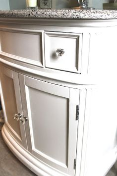 The dark wooden vanity was transformed with Cabinetcoat paint in Cloud White and new glass knobs.