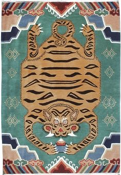 This one has all the traditional elements expected in a Tibetan carpet. The Tiger holding the Jewel of Wisdom is bordered with traditional Tibetan mountain and cloud elements, on a gorgeous green-blue background.