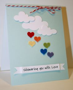 """The """"Showering you with love"""" sentiment was printed from a printer, and the hearts and clouds are die cuts. Layer the cloud several times and it looks like chipboard! These hearts are felt which adds a great texture to this handmade valentines card."""